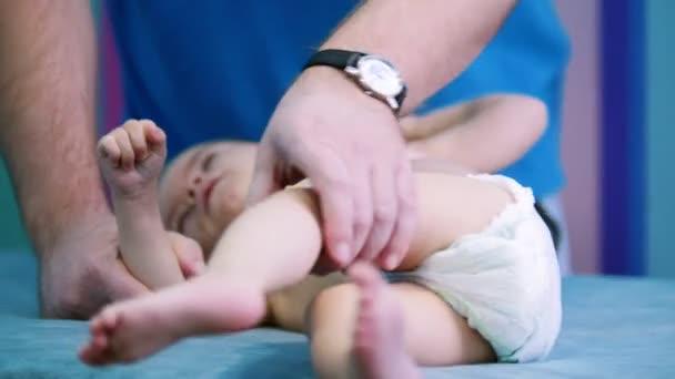 Medicíny klinika. Malé dítě s mozkovou obrnou poruchy klade na lékařské gauči, zatímco doktor dělá cvičení na nohy