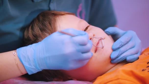 Klinik für Medizin. Ein Baby mit Zerebralparese Krankheit. Logopädische Praxis Massage arbeitet eine Frau mit speziellen Instrument. Nahaufnahme