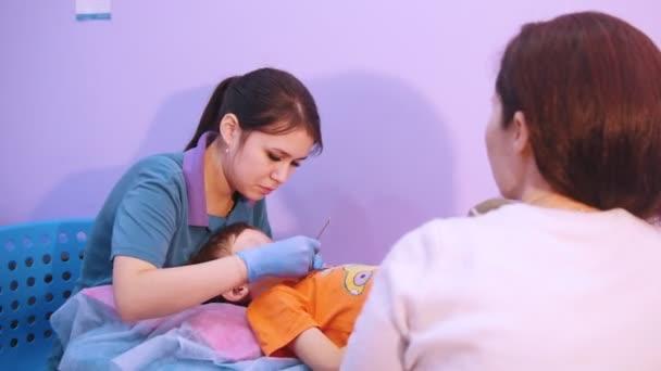 Medicíny klinika. Dítě s mozkovou obrnou nemoc. Projev terapie a masáž, žena pracuje se zvláštním nástrojem v ústech