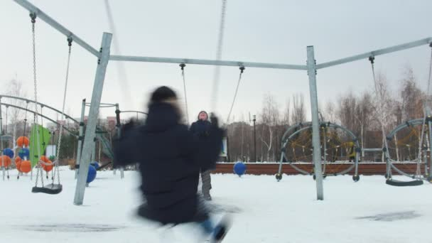 Two young kids having fun on the playground. Swinging