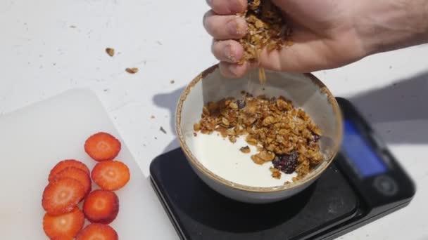 Kde podává snídaně. Bílý jogurt do mísy. Postřikování müsli v jogurtu