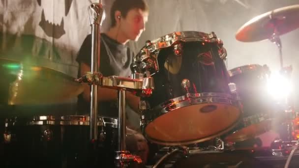 Young man emotionally playing drums in a rock band