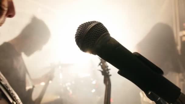Kytarista zpívá doprovodné vokály na koncertě jeho rockové skupiny
