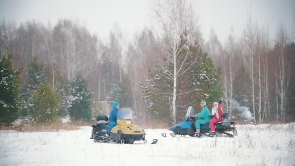 Young people riding a snowmobiles in a winter forest. A woman lighting up a green smoke bomb