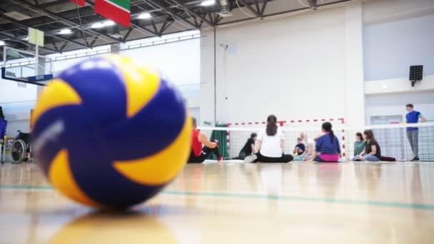 Sport pro zdravotně postižené osoby. Lidé sedí na podlaze a hraje s míčem.