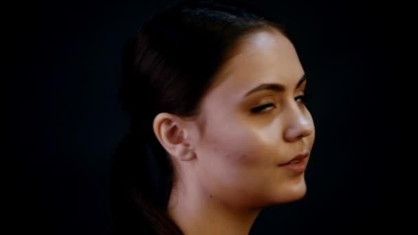 Focení. Portrét mladé krásné ženy modelu s kšandami. Tmavé vlasy, Nahé tvoří. Otočila se a při pohledu do kamery