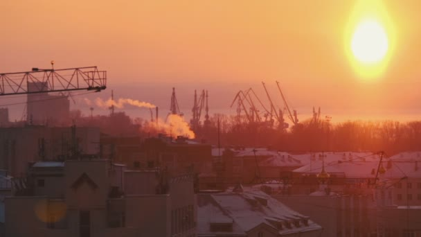 Bright red sunset. Industrial shot. Many hoisting cranes working on the background. A city in smoke