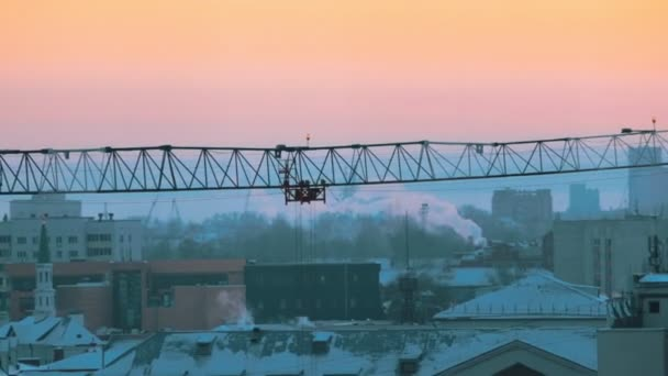 Industrial shot. A construction site in the middle of the city. Hoisting cranes working. Rosy sunset.