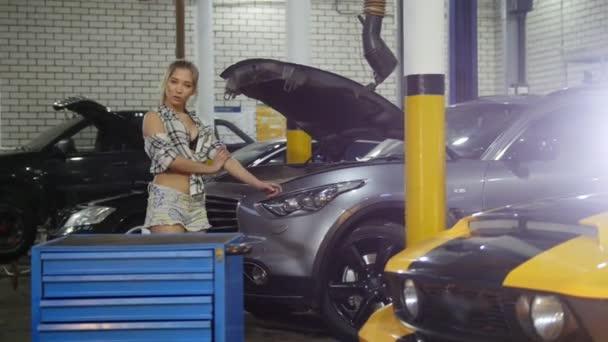 Autoservis. Mladá sexy žena bere klíče od případu na podlaze a sedí na kapotě auta