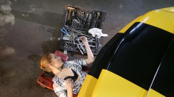 Autoservis. Mladá sexy womanoung sexy žena ze spodní části vozu kouření cigaret, trvá klíč a vrátí do práce
