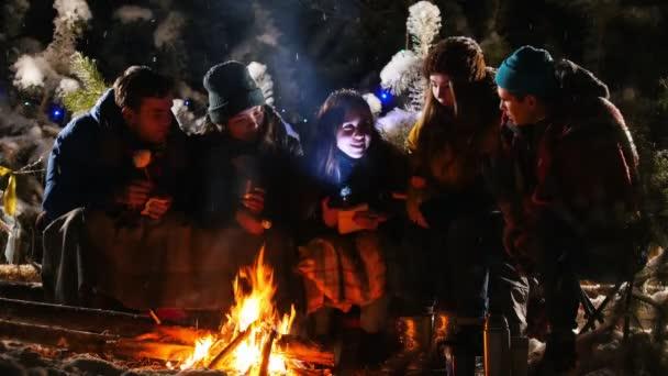 Skupina přátel v zimním lese. Posezení u ohně, poslouchal příběh a strach. Mid shot