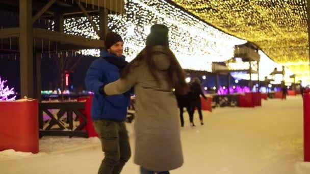 Happy couple ice skating holding hands and then hugging