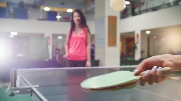 Ping pong playing. Young woman beats a ball with a little racket