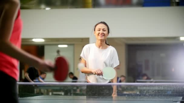 Ping pong playing. Young smiling woman playing table tennis. The woman misses the ball and goes to pick it up