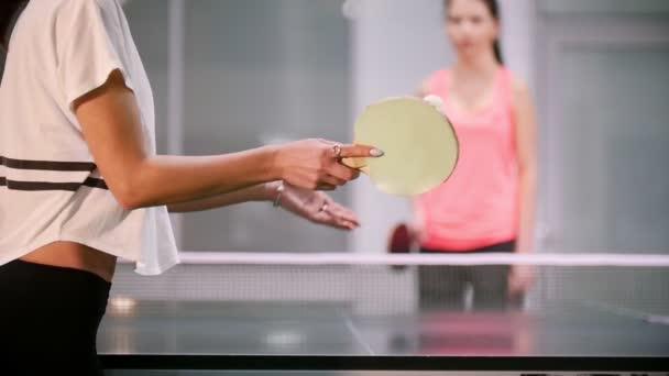 Ping pong hrát. Mladá žena směn míč, její soupeř selže a žena chytí míč rukou