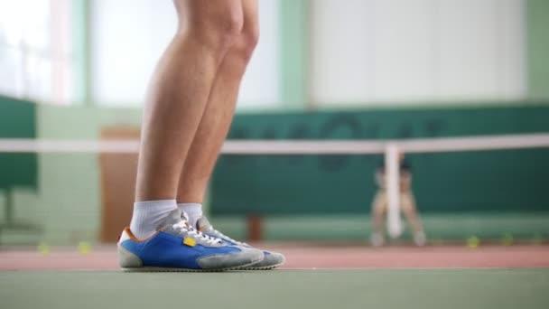 Képzés a teniszpályán. Két fiatal férfi-egy jó formában játszott a tenisz. Láb kék focus csizma