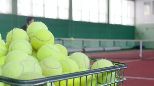 Dva mladí muži hrají tenis na tenisovém kurtu. Školení. Vozík plný tenisové míčky na popředí
