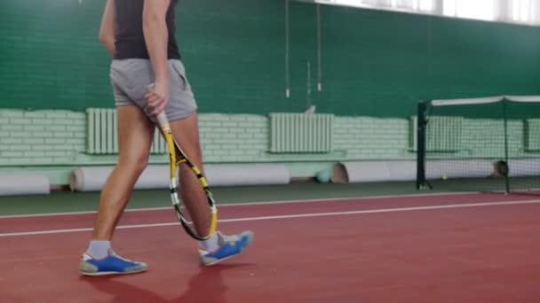 Školení na tenisový kurt. Mladý muž hráč na tenisový kurt. Připravuje pro hru