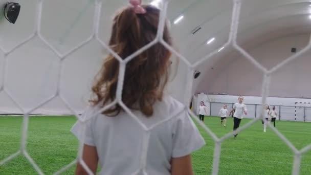 Malé děti hrát fotbal v halové fotbalové arény