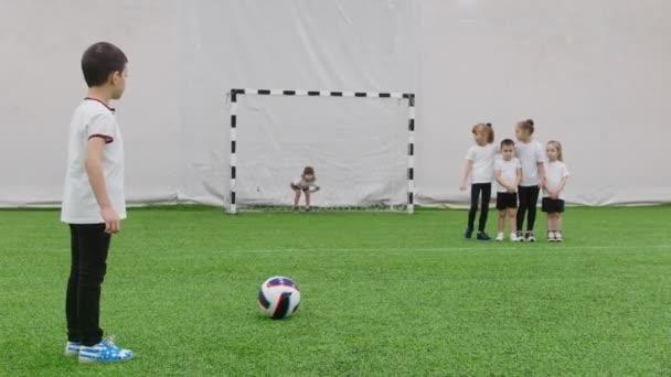 Halový fotbal aréna. Malé děti hrát fotbal. Malá holčička ochrana brány