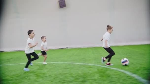 Teremfoci arena. Gyermekek fut a pályán. Egy lány vezeti a labdát