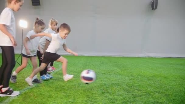 Halový fotbal aréna. Děti začít hrát. Chlapce vede míč