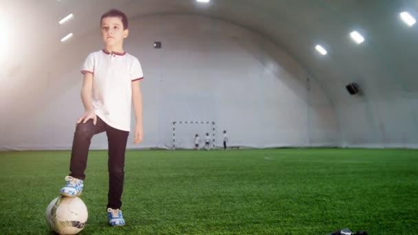 Halový fotbal aréna. Malý chlapec stojící s uvedení nohu na míč