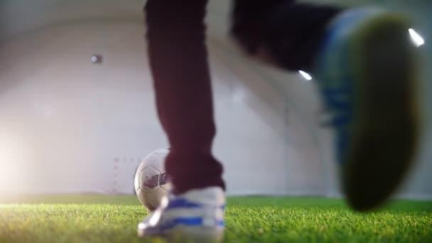 Halový fotbal aréna. Malý chlapec běží směrem k míč a Kopni ji