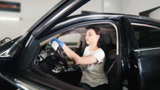 Mladá žena otření volant automobilu