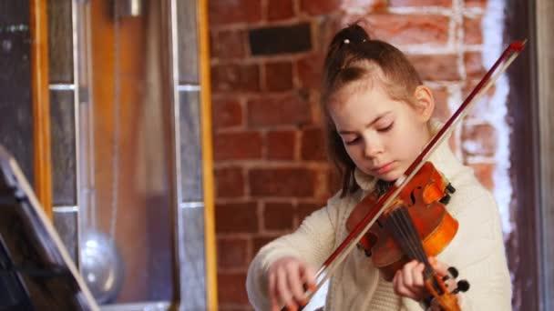 Egy kis zenész lány hegedül fehér pulóver