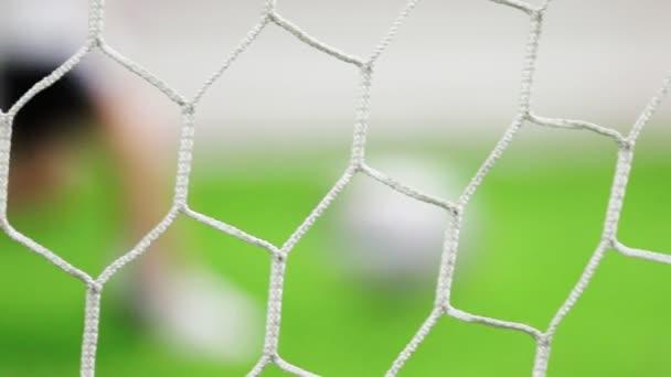 Futball kapu rács a középpontban. Gyermekek focizni a háttér