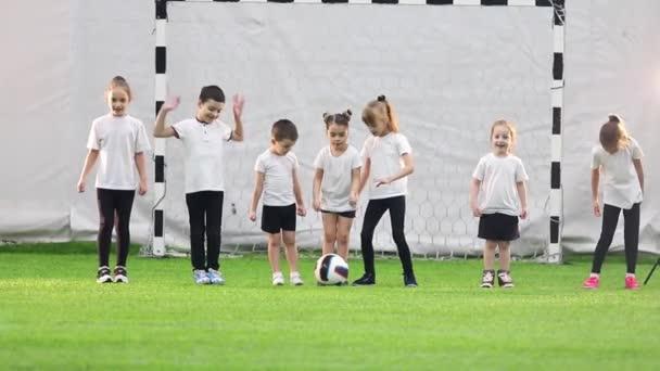 Fußball-Hallen. Kinder stehen Schlange. ein Mädchen tritt den Ball und das Spiel beginnt
