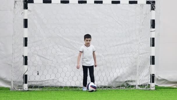 Teremfoci arena. A kis fiú kapuőr rúgja a labdát, és a játék indítása