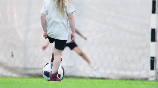 Fußball-Hallen. ein kleines Mädchen schießt den Ball zu den Toren, aber der junge Torwart fängt ihn