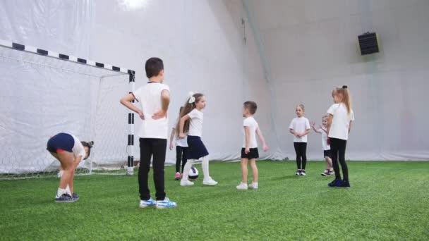 Děti hrají fotbal v Halové Fotbalové aréně. Diskutujeme o taktiku