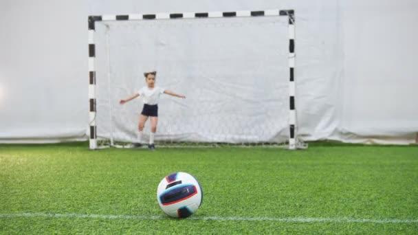 Kinder spielen Fußball in der Fußballhalle. ein kleines Kind tritt den Ball, aber der Torhüter schützt die Tore