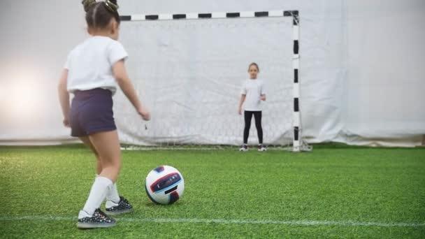 Děti hrají fotbal. Malé dítě s míčem, ale vrátný chrání brány