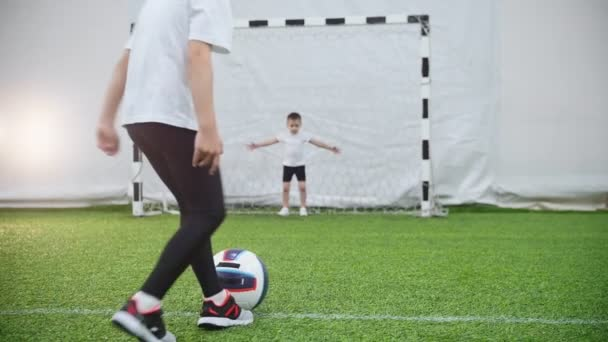 Kinder spielen Fußball. ein kleines Mädchen tritt den Ball, aber der Torhüter schützt die Tore