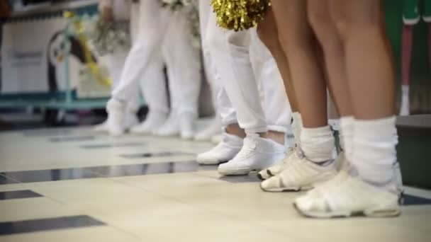 Sport competition. Cheerleading women standing indoors and waving with a pom poms. White socks and sneakers