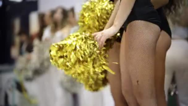 Sport competition. Cheerleading women standing indoors and waving with a pompons