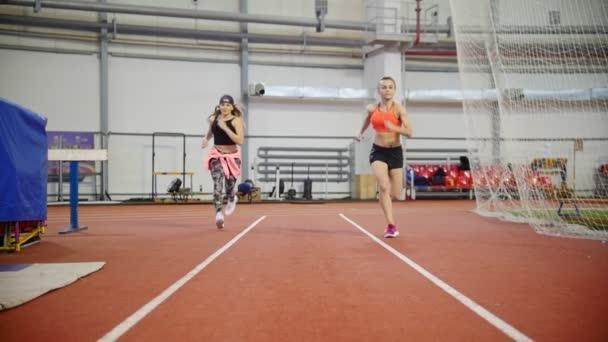 Dvě mladé atletické ženy začnou zobrazovat ve sportovní aréně na Běžecká stopa