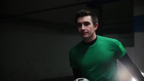 Mélygarázs. Egy fiatal futball ember képzési foci trükkök. Terheléselosztás a labdát