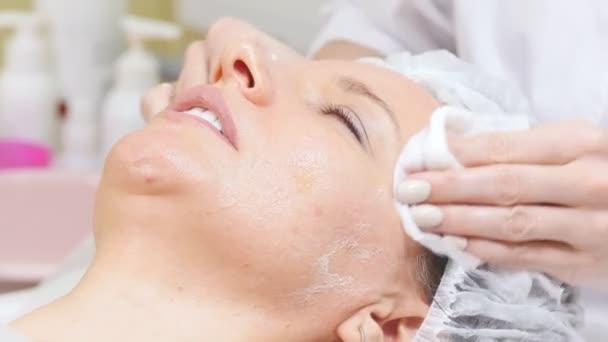 Kozmetikus dörzsöli a krém, az ügyfelek arcon csinál kozmetikai eljárások tisztítást, az arc, a klinika kozmetológiai. Közeli kép: