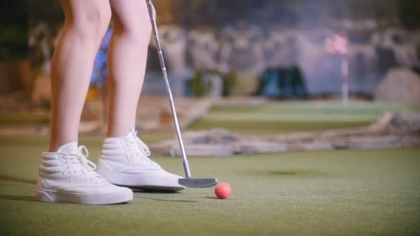 Mladá žena hrát mini golf. Nohy do rámečku