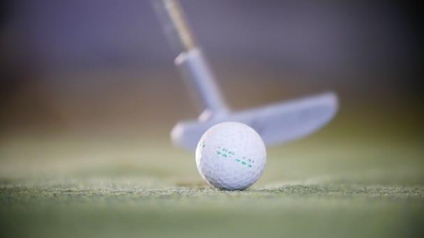 Playing mini golf. The golf stick hitting a golf ball