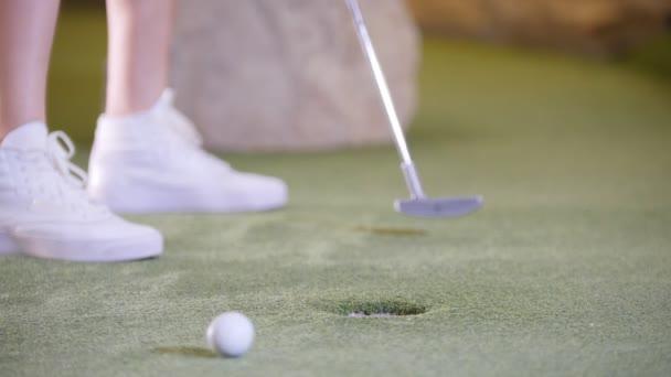 Hra mini golf. Člověk v bílých teniskách, bít golfový míček a zasáhne cíl