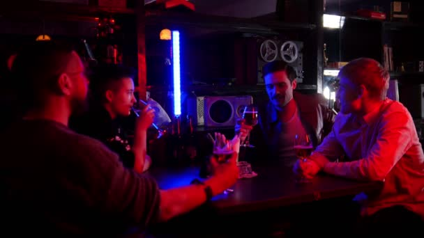Bar with neon lighting. Four friends spending time together