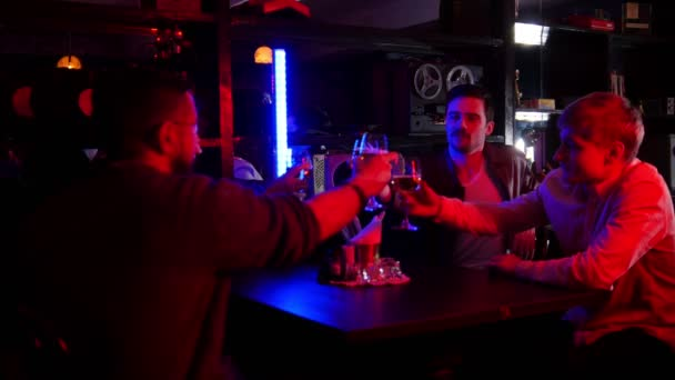 Bar with neon lighting. Friends spending time together, drinking beer. Cheers