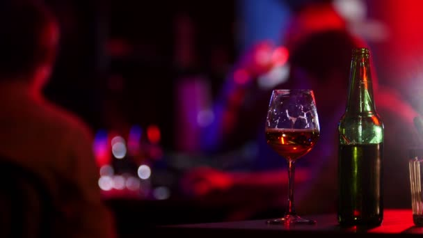 Neon világítás-bár. Company a sört meg. Egy palack és a pohár sört az előtérben