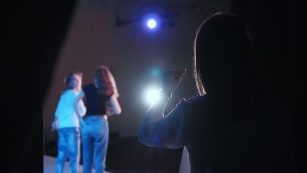 Scéně divadla. Výkon. Dvě dívky na jeviště a žena ze zákulisí přichytí prsty